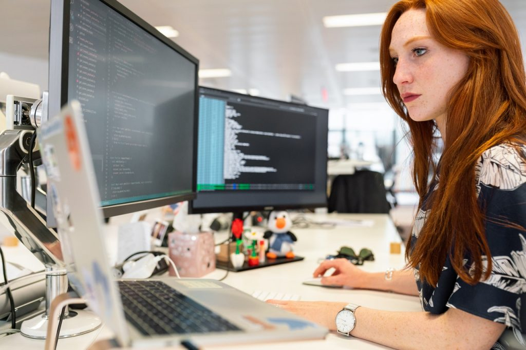 A woman coding software on a computer.