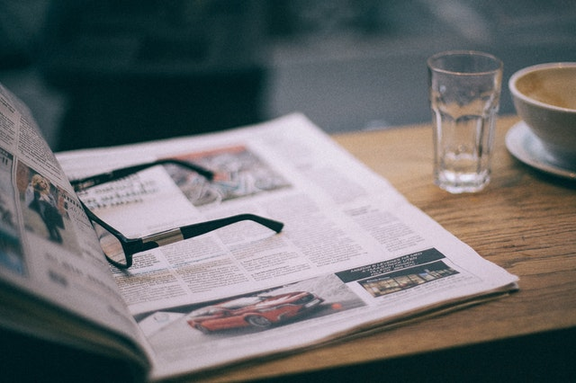 Glasses resting on an open newspaper.