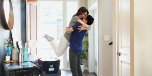Couple hugging after moving into a new home.