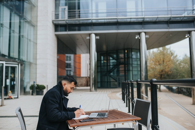 MAN WORKING OUTDOORS ON HIS COMPUTER.